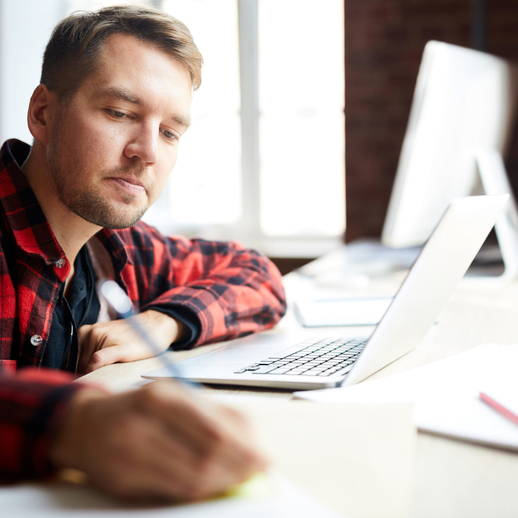 Young student or manager making notes while sitting in front of laptop by desk